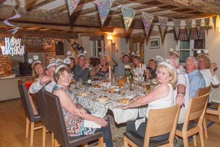 Friends around table to celebrate 60th birthday party at The White House in Crosthwaite, Cumbria