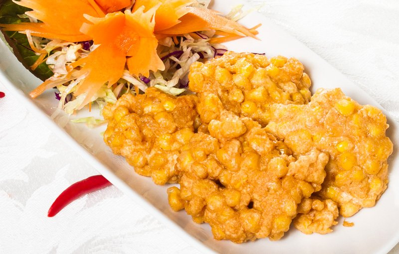 Corn Fritters ทอดมันข้าวโพด (tôt man kâao-pôht), pieces of sweet corn wrapped in batter and deep-fried.