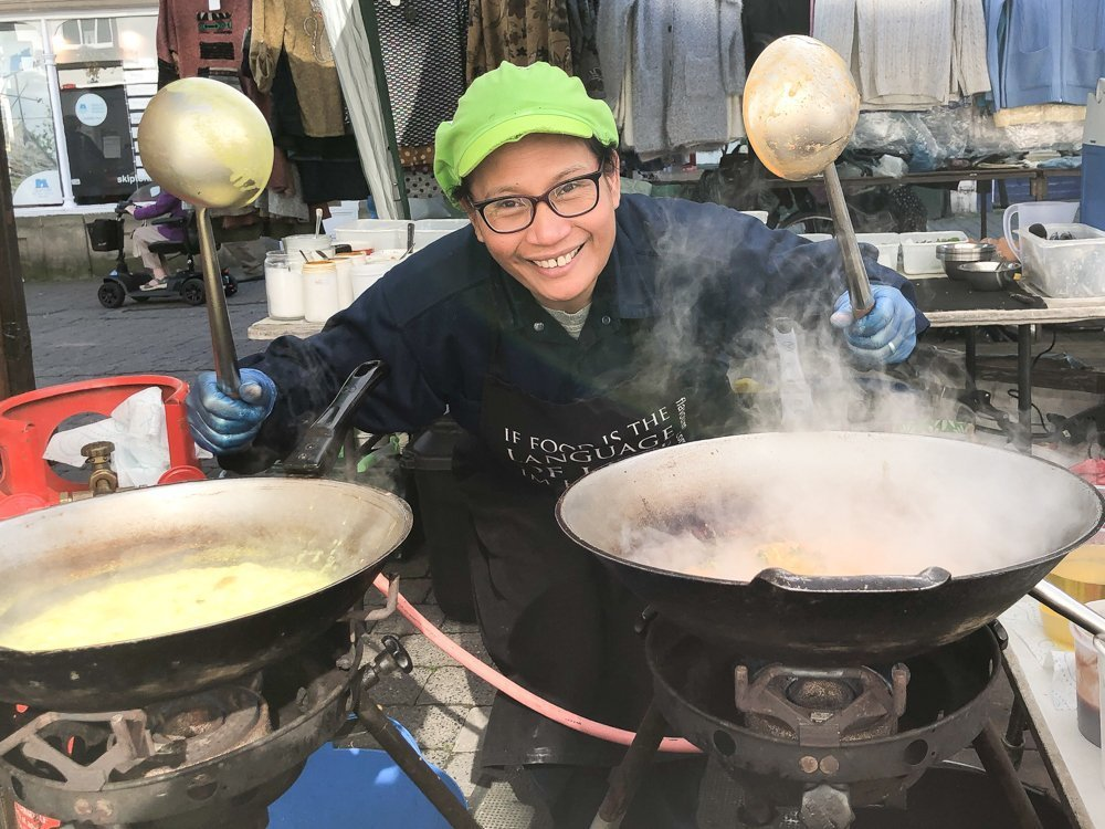 thai chef cooking with woks at thai street food stall