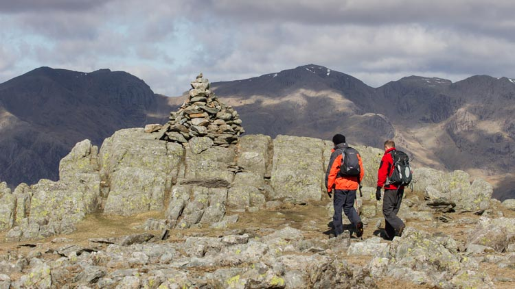 Walkers on the summit of Grey Friar with Scafell and Scafell Pike