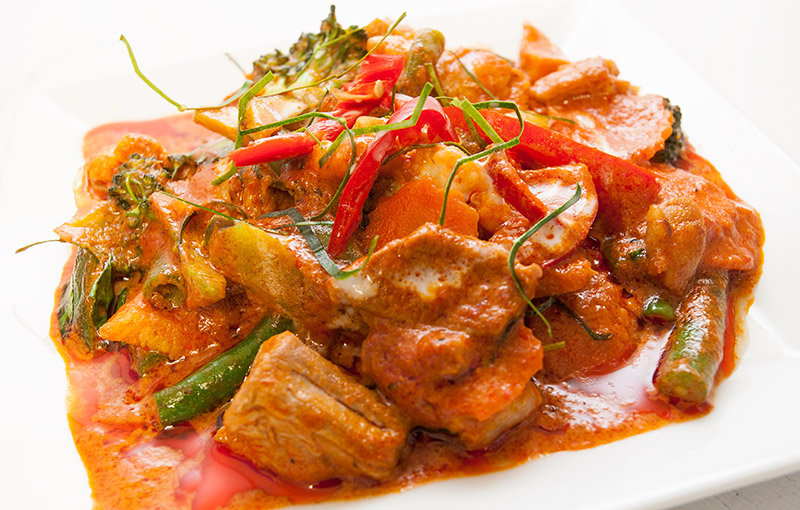A plate of Pad Pet Moo, belly pork with red curry paste from out Thai takeaway menu