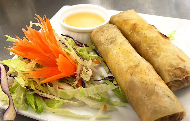 Plate of Thai vegetable spring rolls with a plum sauce dip and garnish