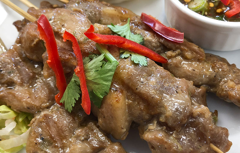 Moo Ping, strips of pork, marinated on skewers and eaten with Thai sticky rice
