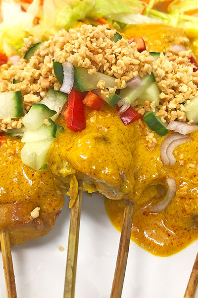 A plate of chicken satay with satay sauce and garnished with cucumber, shallot, peppers, chilli and sprinkled with ground peanuts.