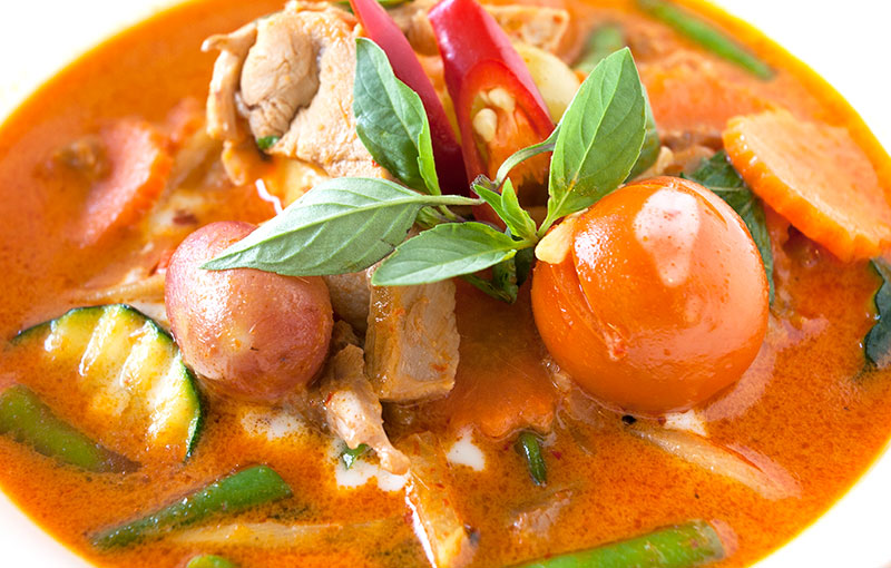 A dish of red curry with duck, tomatoes, grapes, cucumber
