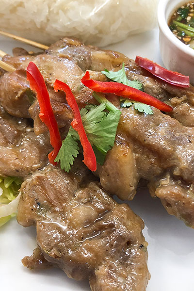 moo ping, thai grilled pork on skewers, served with stick rice and tamarind dip