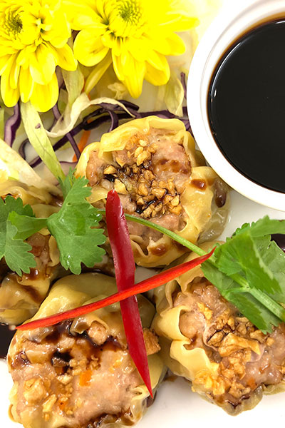 Kanom Jeep, a plate of Thai Dim Sum with soya sauce and garnish