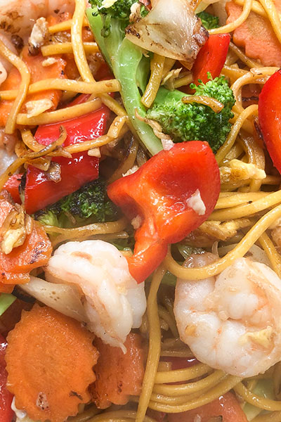 A dish of stir fry vegetable noodles, pàt mèe súa, with prawns and vegetables