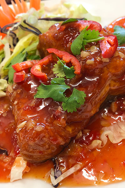 Pla Sarm Rot (three flavoured fish), sea bass, covered in three flavoured sauce, garnished with peppers, chilli, coriander